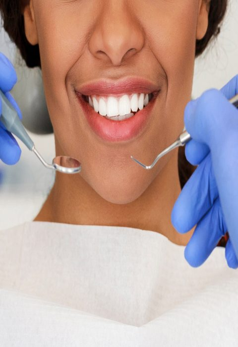 Beautiful african woman smile and dentist hands with dental tools, close up, panorama