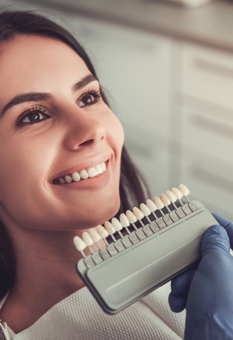 Beautiful young woman is sitting in dentist's chair while doctor is examining her teeth